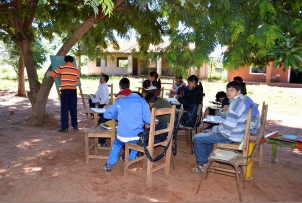 Niños de Yaguareté Forest dan clases bajo árboles, mientras la construcción de aulas está abandonada.